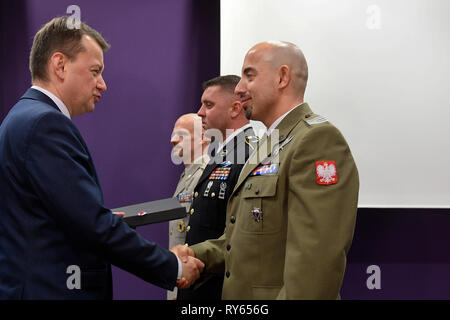 Czech paratrooper Ivo Zelinka (from left), Polish soldier Marcin Kulas and U.S. soldier Corey Speck receive awards from Polish Defence Minister Mariusz Blaszczak, left, in Prague, Czech Republic, March 11, 2019. On September 10, 2009, Speck saved the life of Kulas in the mission in Afghanistan. The two soldiers' story inspired a documentary which makes part of the Polish series 'Veterans. They Escaped Death.'The anniversary of the Czech Republic, Hungary and Poland joining NATO 20 years ago is a major moment for the countries, Czech Defence Minister Lubomir Metnar (not pictured) said on the ev - Stock Photo
