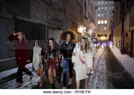Bachelorette and friends walking along snowy urban alley at night - Stock Photo