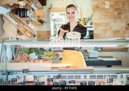 Salesgirl selling cheese in deli or supermarket - Stock Photo