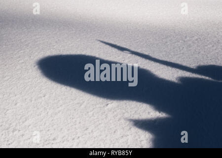 the silhouette of a man on the snow holding a knife in his hand - Stock Photo