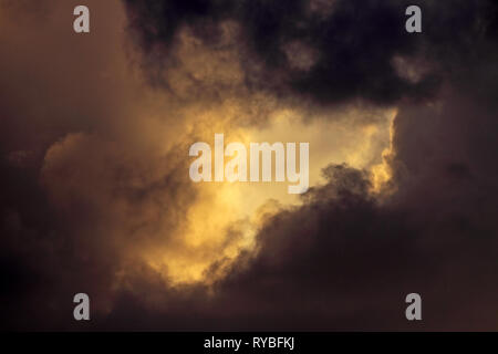 Dark dramatic sky in a stormy evening with an hole of light between clouds - Stock Photo