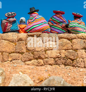 Square photograph of indigenous quechua ladies in traditional clothing with a young boy sitting on an Inca wall in the Sacred Valley of the Inca, Peru. - Stock Photo
