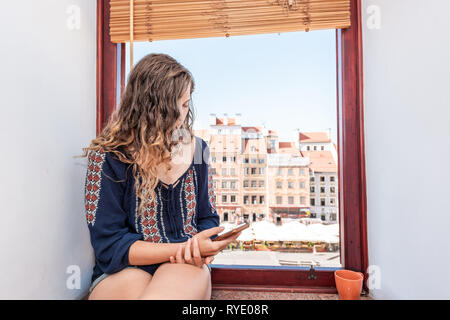 Young woman looking at phone sitting on window sill of apartment with view of old market square in town of Warsaw, Poland - Stock Photo