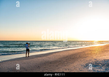 Young man professional photographer taking picture photo of beach sunset in Florida Siesta Key by Sarasota by beach waves holding big camera - Stock Photo