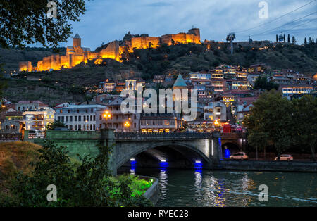 TBILISI, GEORGIA - SEPTEMBER 22, 2018: Colorful evening view of old town and the illuminated Narikala fortress - Stock Photo