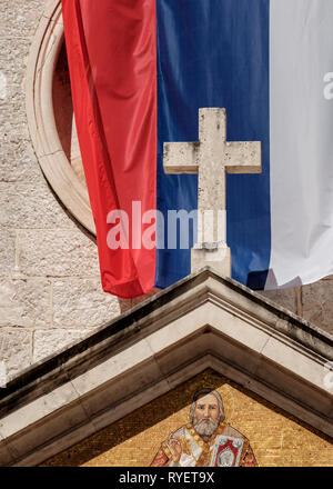A stone cross in front of the flag of the Serbian Orthodox Church Kotor, Montenegro - Stock Photo