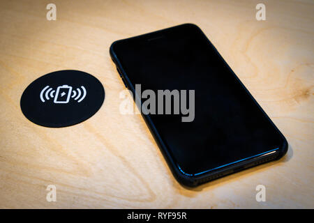 Smartphone charging on a table with a wireless charging pad. Wireless charging in common spaces like airports, cafes and stations concept - Stock Photo