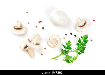 Champignon mushrooms, whole and sliced, shot from above on a white background with pepper and parsley leaves, a flat lay composition - Stock Photo