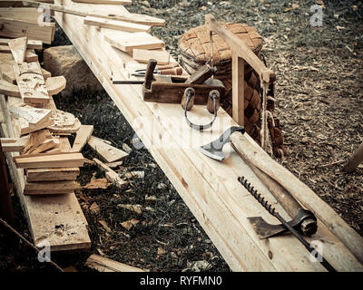 Old woodworking hand tool: wooden plane, chisel ax, and drawing knife in a carpentry workshop on wooden bench ground covered with sawdust background - Stock Photo