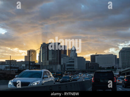 Heavy traffic in downtown Los Angeles: spectacular scenery of golden sun setting behind skyscrapers shot from 101 busy freeway. - Stock Photo