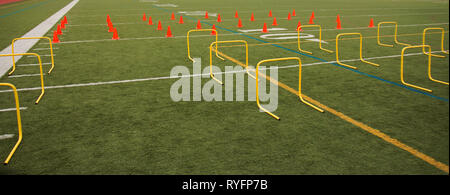 Orange cones and yellow hurdles are set up on a green turf field for speed practice for high school sports. - Stock Photo