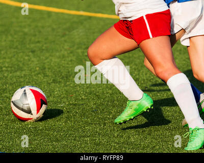 Two girls chasing a soccer ball during a high school game on a sunny afternoon. - Stock Photo