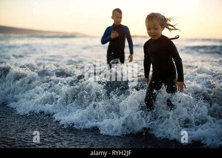 Two young children playing in the surf at sunset. - Stock Photo