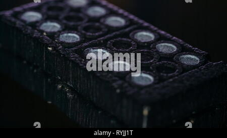 Two dominoes piled up on a macro shot with the small black and white holes on it - Stock Photo