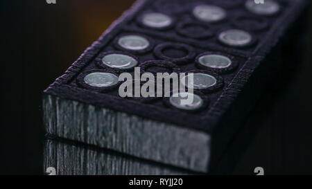 The black and white holes of the dominoe on a macro shot piled up on the table - Stock Photo