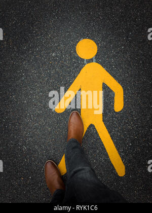 pedestrian sign on pavement with feet - Stock Photo
