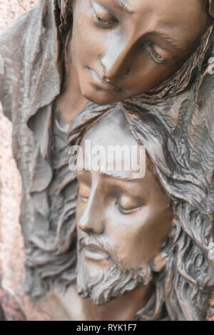 Bas-relief in bronze representing The Pity of Michelangelo. Faces of Holy Mary mother and Jesus Christ after the Crucifixion. - Stock Photo