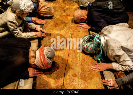 Christian pilgrims worshiping at the Holy Sepulcher, Jerusalem, Israel. - Stock Photo