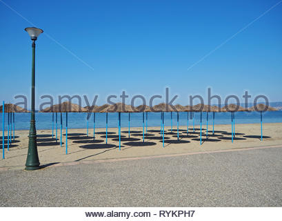 abstract view of public post light along with sun shade umbrellas with their shadows on the sand at the seafront - Stock Photo