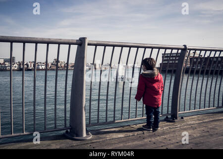 Small boy in red coat looking at boats and yachts Portsmouth harbour from the bridge at Gosport, UK - Stock Photo