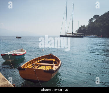 Two wooden fishing boats moored in small marina at Mediterranean village in Italy on background of sailboats and seascape. - Stock Photo