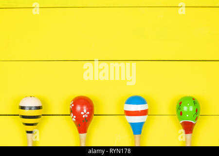 Colorful maracas  on yellow wooden boards background. - Stock Photo
