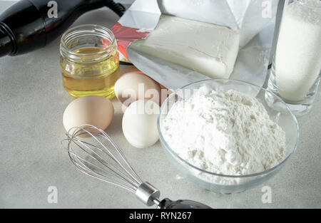 Flour and sugar in a glass container, eggs and butter on a white table. - Stock Photo