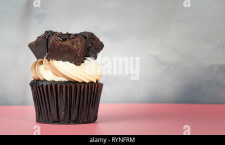 Brownie Cupcake on pink table with gray copy space - Stock Photo