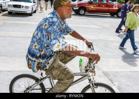 Miami Florida man middle aged cyclist bicycle bike riding no safety helmet transportation - Stock Photo