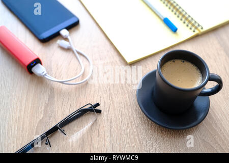 The smartphone is charging from the poverbank. Cup of coffee, diary, pencil and glasses on the table close-up - Stock Photo