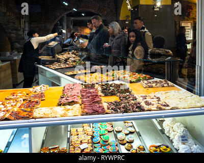 BERGAMO, ITALY - FEBRUARY 25, 2019: view through street window with local fast food of people in bakery cafe buying sandwiches for lunch in Citta Alta - Stock Photo