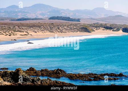 Blue ocean below with a close by rocky shore, white waves rolling on sandy beach beyond under hazy sky. - Stock Photo