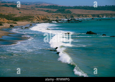 Ocean waves breaking onto shoreline with cliffs and rolling hills beyond under bright blue skies. - Stock Photo