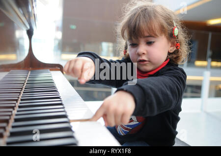 little girl having fun playing the piano - Stock Photo