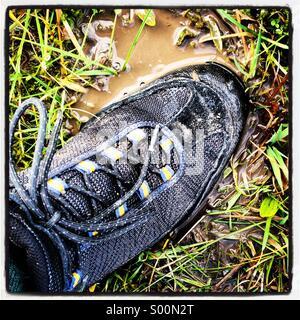 Foot on waterlogged ground due to UK flooding - Stock Photo