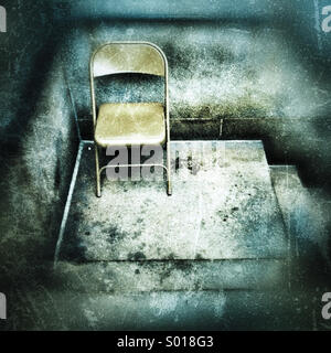 A metal folding chair sitting on a distressed looking cement stoop - Stock Photo