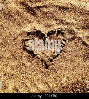 Heart made of pebbles in the sand. - Stock Photo