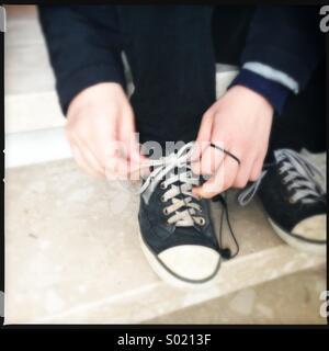 Boy fasten his shoes - Stock Photo