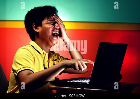 Asian teenager boy working or studying on a laptop computer and laughing hard - Stock Photo