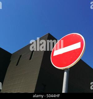 No entry sign against a blue sky and modern black building - Stock Photo