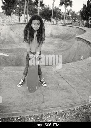 A seven-year-old girl with her skateboard at a city park in Florida. - Stock Photo