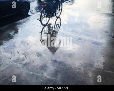 Cyclist on wet street with reflections - Stock Photo