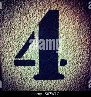 Number 4 stencil painted in black on a textured wall - Stock Photo