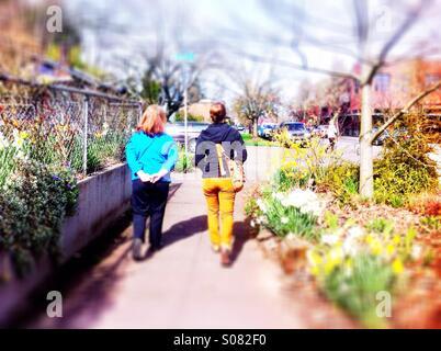 Two women walking on sidewalk in spring - Stock Photo