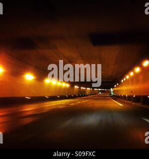 This is a motion blurred image of a car moving through a tunnel in Paris. - Stock Photo