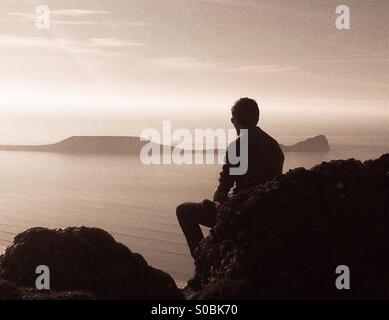 Teenager sitting on a rock overlooking  the sea near Worms head, Gower. Side view silhouette. - Stock Photo