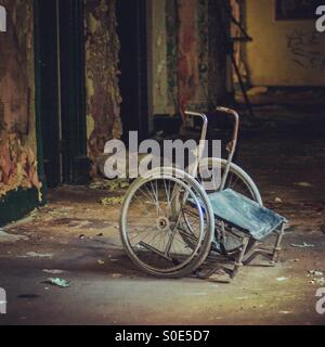 Eerie wheelchair in abandoned building - Stock Photo