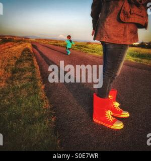 A mom wearing red boots watches while her little boy runs away on the path in the late afternoon. - Stock Photo