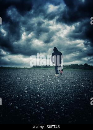 Hooded boy running away - Stock Photo