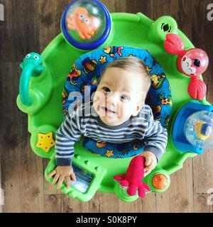 Photo from above  of a smiling 9 months old baby boy , who is sitting in his toy jumpy chair , having a great time, - Stock Photo